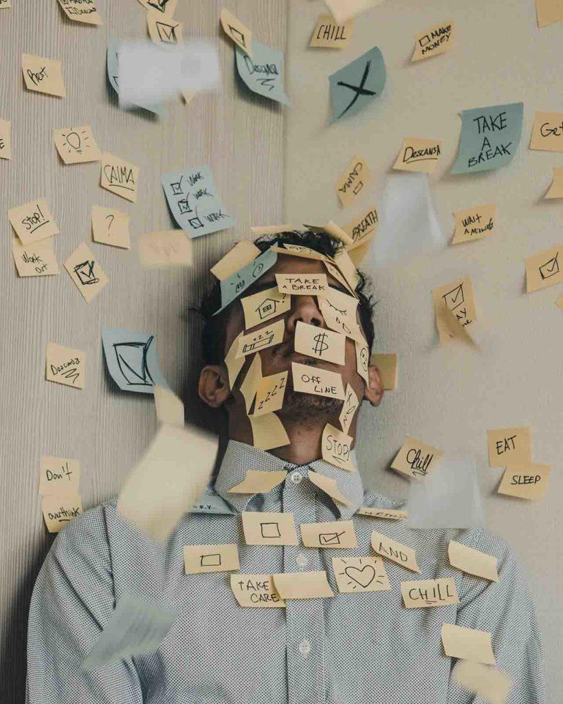 Hombre con muchos post-it que ilustran su estrés