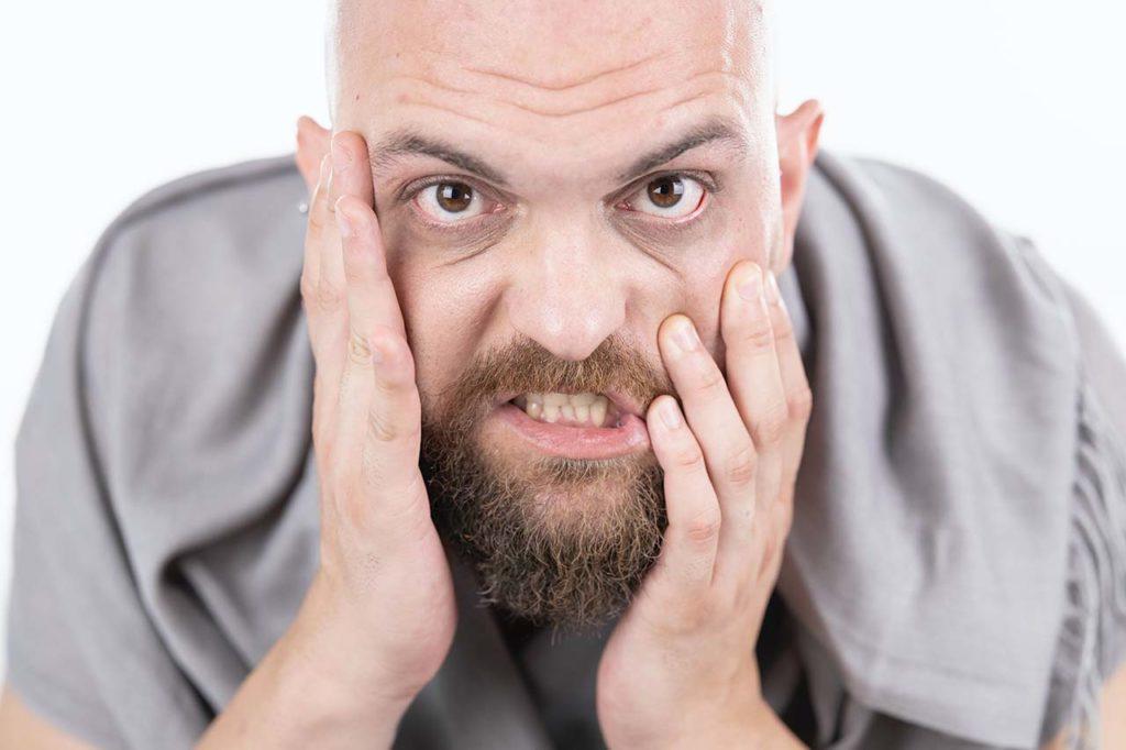 Hombre apretando los dientes por estrés