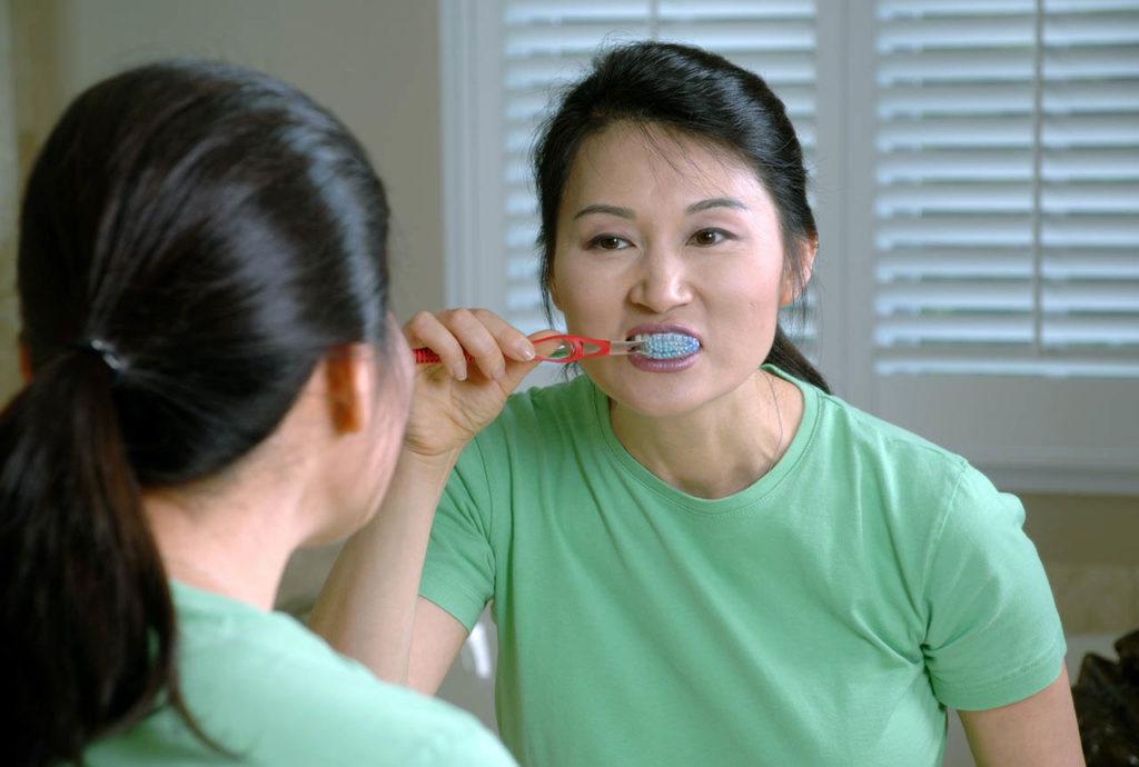 Lavarse los dientes frente a un espejo