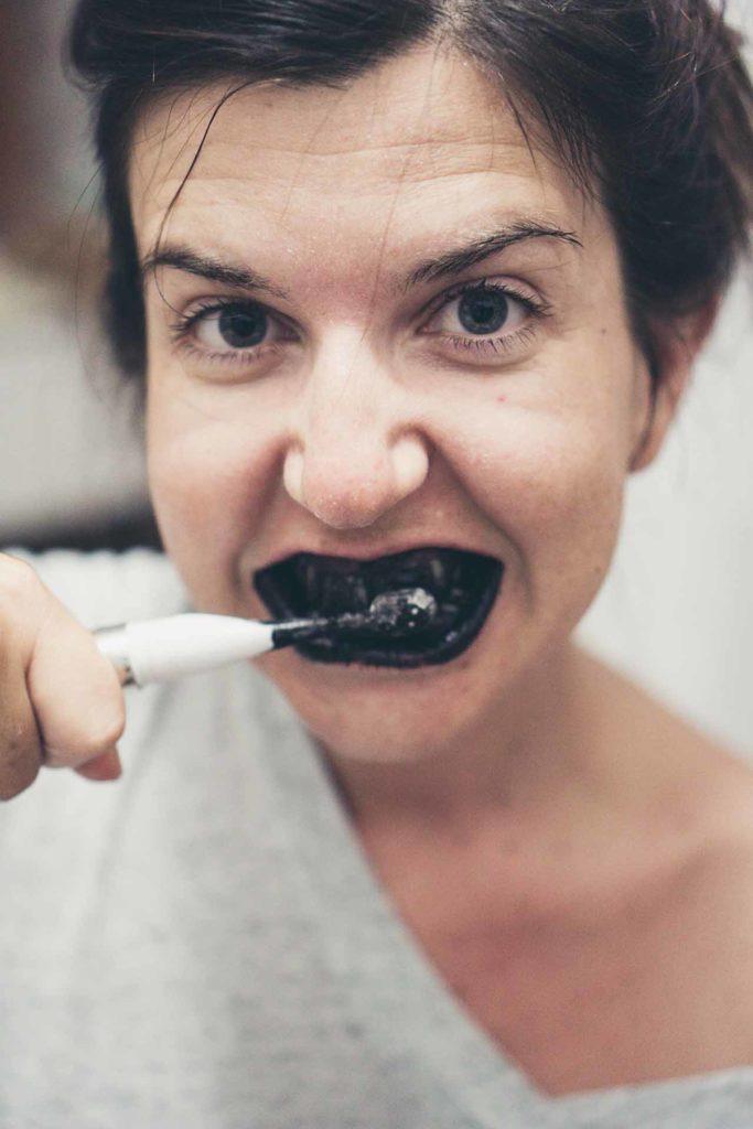 Mujer que se intenta blanquear los dientes con carbón activado